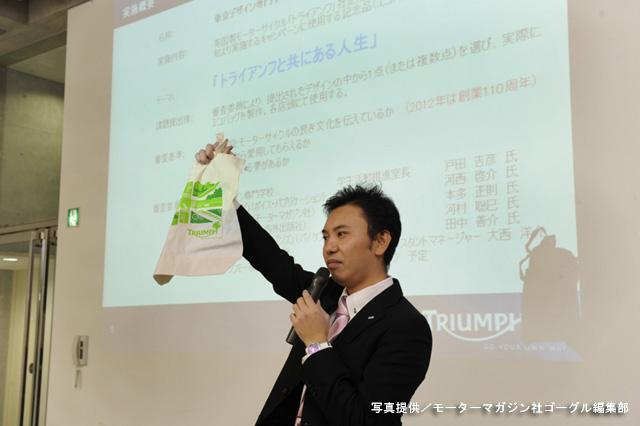 オリエンテーションはトライアンフ ジャパン 大西氏により進められた。手に持っているのは昨年の『最優秀賞』作品。