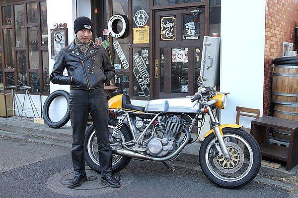 愛車のSR400はエンジンを見ないと何だか分からないほどのカスタムですね。いや~個性あってインパクト大! で、オーナーのファッションは?ダブルのライダースを羽織り、襟元は豹柄でコーディネイト。柄がアクセントになっていて◎。ファッションを楽しんでいるのが伝わってきます。バイク乗りには首元の防寒性とファッションのアクセントとしてダブルでお役立ちするアイテム。ジャケットのゆるめなシルエットや、股上の深いボトムスは現代のトレンドと少々かけ離れて古い印象ですが、これは狙ってコーデしているんですよね?