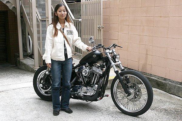 """マスタングタンクやローダウンにより、車体をコンパクトに見せているKEIKOさん。愛車は悪そうなイメージで、とても女性が乗りそうには見えませんね~。で、ファッションはヘルメットメーカーの""""Mc Hal""""とプリントが入ったジャケット。バイクのカスタムしかり、ご自身の好みがハッキリされていらっしゃるのでしょう、ファッションもどっぷりバイク好きが伺えます。"""