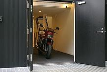 玄関がガレージスペースの出入り口を兼ねる。扉は両開きになっており、開口部は1.4m。幅広ハンドルでも心配なし。