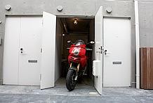 両開き扉の玄関を兼ねたバイクスルーム。大型バイクが1台収まるスペース。250ccオフロードバイクでも2台収めるのは少々厳しそう。