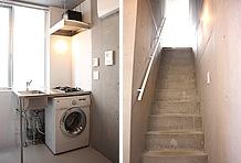2階のキッチンスペース。2口ガスコンロの下にはドラム式選択乾燥機が設置されている。オシャレなコンクリート打ちっぱなしの階段、壁。