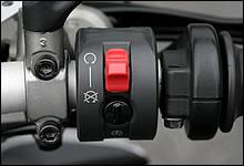右側ハンドルスイッチには、セルスターターとキルスイッチが配される。赤い凸部がスライド式キルスイッチ、黒く丸い部分がセルスイッチ。スライド式のキルスイッチをオンにすると、セルスイッチが隠れて押せなくなるユニークな仕組み。
