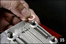 クランクケースに向かって正面左下のスタッドボルトはオイルの立ち上がり通路となっているから、ナット締めつけ座面に銅ワッシャーをセットした後に、キットの袋ナットを手締めで取り付ける。