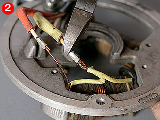 コイルベース裏側で、加工するコイルのハーネスを切断する。黄色の被覆をかぶった方がライティングコイル、オレンジ色の被覆はチャージコイルだ。表側のアースコードも切断する。