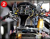 ②新気はヘンドパイプを貫通して導入される。市販車同様の構成だが、ダクトやブラケットがカーボン製となり、マニエッティ・マレリの電装品ともどもワークスマシンらしい機能美を醸し出している。メーターパネルは2D製