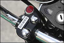当時はどのメーカーも速度警告灯は後付けのように装着されていた。76/77年当時の力ワサキは、ハンドルポストの締め付けと共締めにして、警告灯ブラケッ卜を締め付けていた。