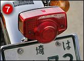 スーパーカブとも同形状なテールランプを装備。ただし両サイドにはオレンジ色のリフレクターが付く。69年の新車登録当時のナンバープレートが付く。僕の愛車は2オーナー車。長年所有し続けてこられた理由が、このナンバー存続にある。