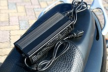 専用充電器はシート下のボックスにも入る大きさです。01CTは4.5時間で充電が完了するので、せっかちな人にもオススメ。