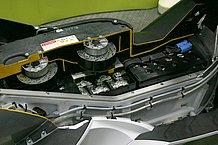 マスの集中と低重心化を狙い、股下部分に大容量ニッケル水素バッテリーを搭載。カットモデルを見ると、その大きさが良く分かりますね。バッテリー温度が上昇すると、上部にある2基の小型ファンが作動してバッテリーを冷却する仕組みで、さらにはフロント側からもダクトによって走行風が導入されています。熱対策には気を使っていますね。ただ、バッテリースペースが大きいために、フットスペースは幾分狭くなっていました。