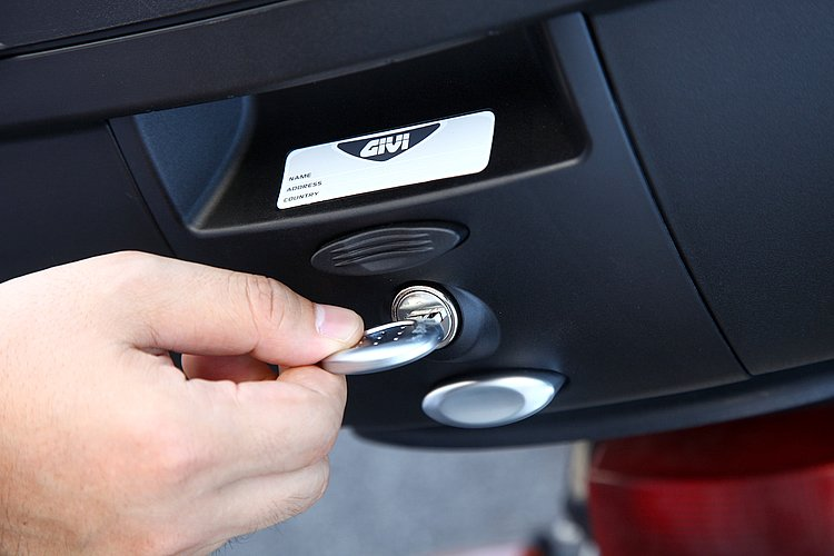 トップケースの固定&施錠、そしてフタの施錠も1本のキーで行えるのがGIVIの特徴。フタを施錠しないとキーが抜けないので防犯性も高い。他モデルでは赤いロックボタンも黒とシルバー。