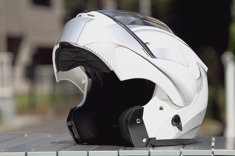 アゴの部分をガードするフェイスホルダーは、ワンタッチではね上げられる仕組。単なるフルフェイスでなく、口元がワイドに開くシステムタイプのヘルメットなので、休憩時などにも重宝する。