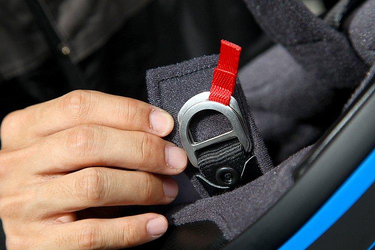 もっとも一般的なDリング式を採用。適切な位置でしっかりとアゴ紐を固定することができる。Dリングには第三者がヘルメットを脱がせやすいよう、明るい赤のリボンがつけられている。