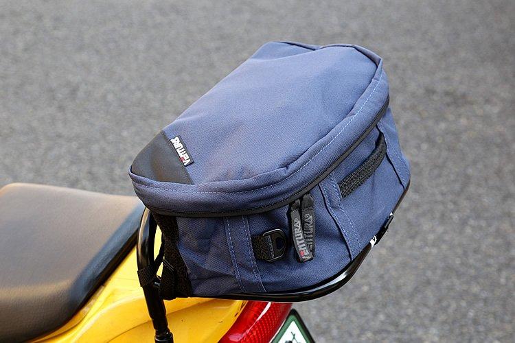 低めの背を持つスポーツラックに装着された「スポーツパック 2」。10Lという手頃な収納力で、持ち運びに便利な把手が付く。着脱可能なショルダーストラップも付属。