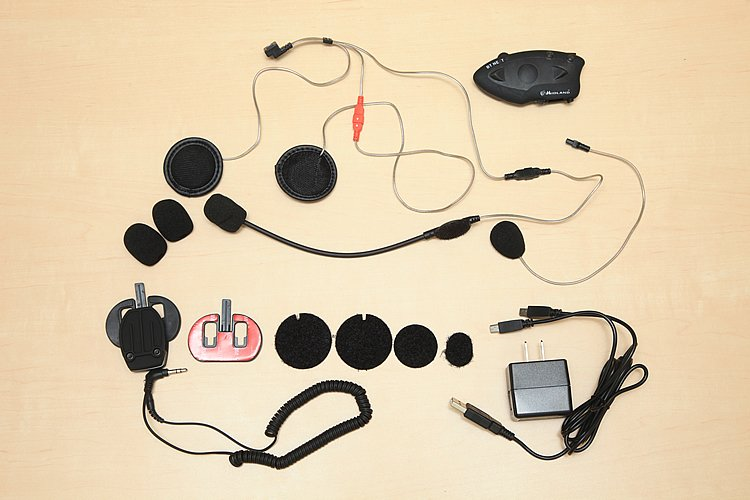 セット内容は本体、マイク(フルフェイス用、ジェット用各1機)、予備マイクスポンジ、ステレオスピーカー、取付ベース(クランプ、両面テープ各1個)、スピーカー取付用スポンジ、充電用ACアダプター(USB)、外部入力用ケーブル(ミニピンジャック)と必要十分。