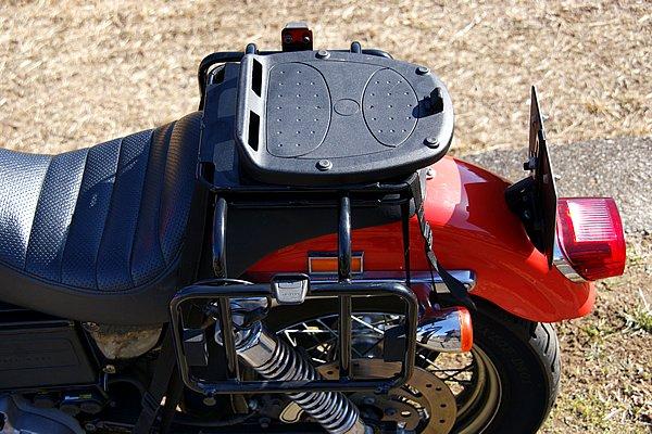 4本のベルトで固定するので、狭いスポーツスターのタンデムシートにも安定して装着できる。トップケースのベースはオプション。