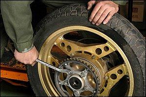 ドリブンスプロケットの取外しは、タイヤを地面に立てた状態でナットを緩めると作業がスムーズです。純正では、ネジロックを使用して高トルクで締め付けられていることも多いので注意しましょう。