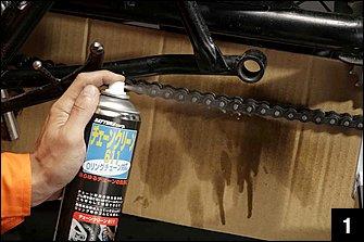 グリス給油時の基本は「ドライブチェーンを暖機」しておくこと。具体的には加減速を繰り返しながら近所を数キロ走ると良い。スプレー前には汚れ防止のダンボール壁を立てる。