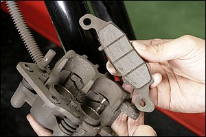 ブレーキパッドの残量確認は、一旦車体からキャリパーを外してしまうのが確実だ。同時に摩擦材表面の清掃や面取りを行なうことでブレーキの鳴きや摩擦材の欠けを予防することができる。