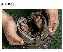 ブレーキパネルから古いシューを取り外す。シューはお互いに強いスプリングで引っ張られているので、弾かれないよう両側をしっかり掴み、力を抜かずゆっくり起こす。