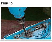 タンクに向かってドリルを立てるとは自虐的だが、ポンチマークを狙って、一文字ドリルで溶接部を削り取る。ドリルをスリコギ運動させて、刃の外周でプレート部をカットする。