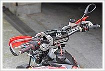 ハンドガードはサイクラのCRMフレームキットを使い、プラスチック部分のみレーステックを取り付けている(バーエンドマウントタイプ)。ハンドルはファットバーに変更。頑丈な作りもオフロードバイクの特徴だが、どうしても転倒によるレバー類の破損があるので、ガード類は必須。