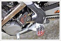 """スプロケットカバーは、ドリップレーシング製をセレクト。""""カーボンで出来ていて非常に軽量""""、というところよりも見た目が良いので選んだ、との事! ステップはDRCのモタードフットペグを使用。赤い部分が樹脂製スライダーになっていて、バイクをバンクさせた時に地面と当たってすり減ってもその部分だけ交換できるというもので、MOTO1ライダーの注目度も高い。ステップを擦る程バンクさせられる人専用商品(笑)。"""