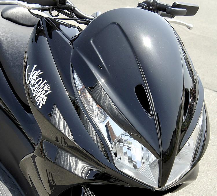 PCXの顔まわりを2灯化してシャープに演出するフェイスは、ビッグスクーターで人気のデザインをPCX用として落とし込んだ一品。適度なボリュームを与えるサイドカウルやリアスポも小技が効いている。