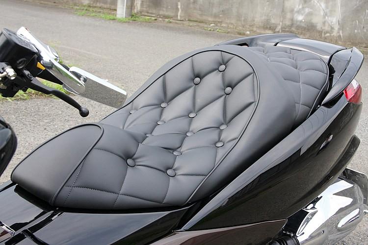 光沢を抑えたレザーを使い、クロスステッチ&ボタン処理を行ったシートは、上質感が漂うラグ方面の人気手法。大型タイプのシートが主流のビッグスクーターにおいて、シート張替えこそ費用対効果が高い。