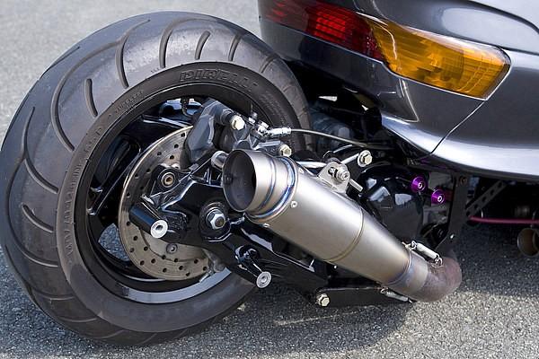 タイヤ一個分延長したド迫力のホイールベースだが、リンクサスによりサスペンションとしてもちろん機能する。チタンのショートマフラーや、前後のウインカー色とのバランスを考え、あえての前期テールがまた渋い。