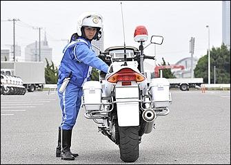 体力・体格面でハンデのある女性でも技術を身につければ、このように体をバイクから離して後進することもできる。上体とともに足先を進行方向に向けると押しやすい。