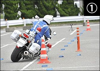 白バイが訓練で行う8の字は走路がマーカーで規制されているのが特徴。コーナー入口では前後ブレーキをフルに使いつつ車体を傾けながら進入していく。