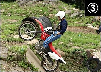 後輪が斜面に当たったらスロットルを緩める。ここで加速し続けようとすると捲れて失敗しやすい。ハンドルに腰を当てるぐらいのイメージで上体を前に引き寄せていく。