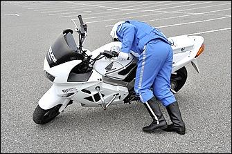 ヒザを車体の下に入れるようにしながら、ハンドルと車体(バンパーやフレーム)をしっかり持って脚力で引き起こす。上体ごとバイクの反対側に押し出すイメージだ。