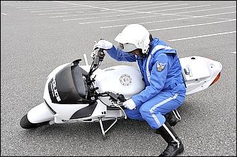 両手でハンドルを持って引き起こす方法。ハンドルを切って、ヒザを車体の下に潜り込ませるように入れて腰をシートに密着させる。体が小さい人や軽いバイクなどに有効だ。