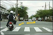 交差点で信号が青に変わるのを見計らって、左からすり抜けしてきたスクーターが飛び出してきました。対向車線の右折車は先に曲がってしまおうと焦っています。典型的な「右直事故」のパターンですよね。前方に駐車車両があるので、スクーターは急に車線変更してセンターに寄ってくるかもしれません。
