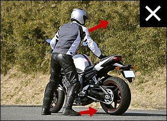 バイクに対して体の正面を向けて立つと、押すときに右手に力が入りにくくなります。また「カニ歩き」になりがちで、足がもつれるなどかえってバランスを崩しやすくなるので注意。左写真と上体や爪先の向きを比べてみてください。