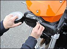 ヘッドライトやテールライト、ウインカーなどの灯火類には、転倒時の飛散防止のためガムテープなどでテーピングを施しましょう。割れた破片などをタイヤが拾うとパンクすることもあり危険です。ただし、何日もテーピングしたまま放置すると固着して剥がしにくくなるので注意。帰りはテープを剥がすことを忘れずに!