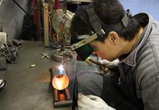 ベリアルの工場では各種工作機械を備え、一部のパーツを除き開発から製造まで自社で一貫して行える体勢を整えている。工場内には、金属加工用の大型機材や、溶接機などがズラリと並べられている。その中で目立つのが、マフラーやチャンバーの製作に使用される治具類。治具は、それぞれの商品に合わせた専用品が必要。オーダーメードで造られる、治具の製作には当然コストもかかるのだが、精度が高く品質が均一な製品造りには欠かせないものだ。パーツ製作に携わるスタッフは、皆熟練した職人ばかり。各々が高い技術を持ち、また、品質向上に向けた高いモラルが感じられる製造現場だ。