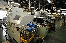 1階の工場には、削り出しを行うNC旋盤が約20台設置されており、その片隅には素材となる真鍮やステンレスの棒材が太さに分けられて整然と並べられている。