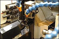 ジェットニードルを削り出すために、真鍮の丸棒をNC旋盤にセットする。ホース状の物は、切削油などを素材に流すための物だ。セットが完了したらNC旋盤の蓋を閉じる。