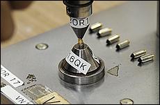 ケース内にスプリング、ピンを入れて最後に専用の機械でカシメてニードルバルブの完成。カシメ作業は1つ1つ手作業で行われている。器具には様々な大きさがある。