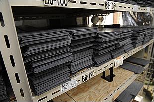ガスケットは板状の紙質等の素材から作られる。もちろん耐ガソリン性のある物で、工場内にはさまざまな厚みや組成違いが用意されて幅広い車種に対応している。