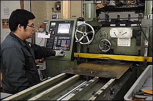 機械にガスケットを打ち抜くための「刃」をセットし、板状の素材をプレスすることで製作していく。打ち抜かれると素材が奥に送られて、次々とガスケットが作られていく。