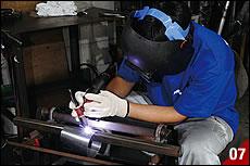 チャンバーボディのテーパー部分を巻き終えたら手作りの半自動溶接台の上に巻いたピースを載せる。トーチを持つ手は固定したまま、フットペダルで自動的にピースを移動させて一直線に溶接する。