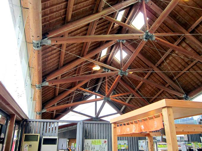 特産品販売コーナーの屋根組みは地元の杉丸太を使ったスケルトンログ工法で組み立てられいます。圧縮力を杉丸太で持たせており、柱の無い大きなスパンをつくっています。