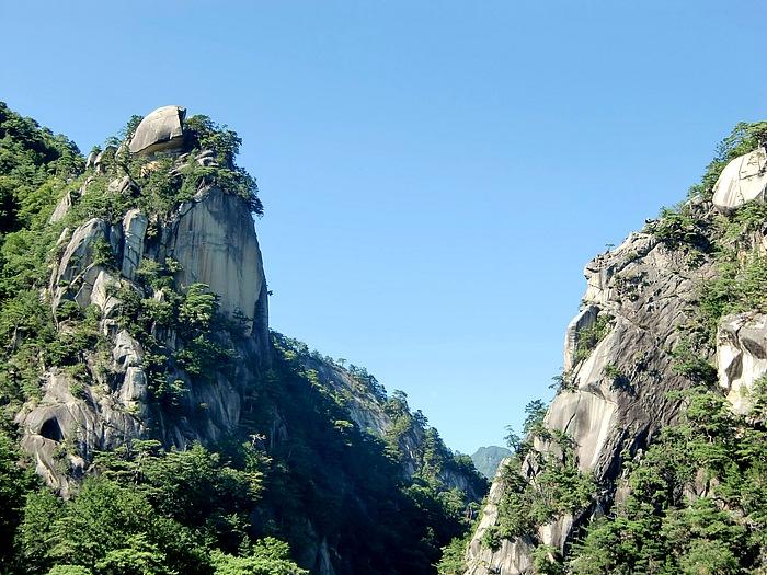昇仙峡の主峰「覚円峰」。水面から垂直に屹立する高さ約180mの頂上では、その名に冠されている僧の覚円が修行したと言い伝えられている。前日の雨雲に煙る眺めも美しかったが、山肌が紅葉すると一段と美しくなる