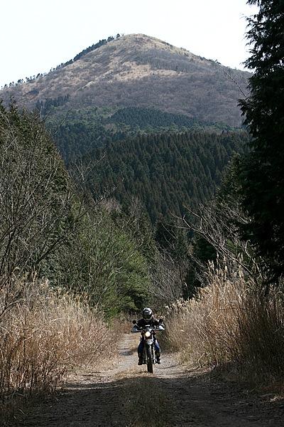 林道大分中部線は東側10kmが舗装、西側10kmがダート。写真のバックにそびえるのは城ヶ岳、ここでだいたい1000mラインを走っている。このあと抜けるような風景があらわれ、由布岳も遠望。6月~10月ごろには、山々や草原が眩しいほどの鮮やかな緑に染められる