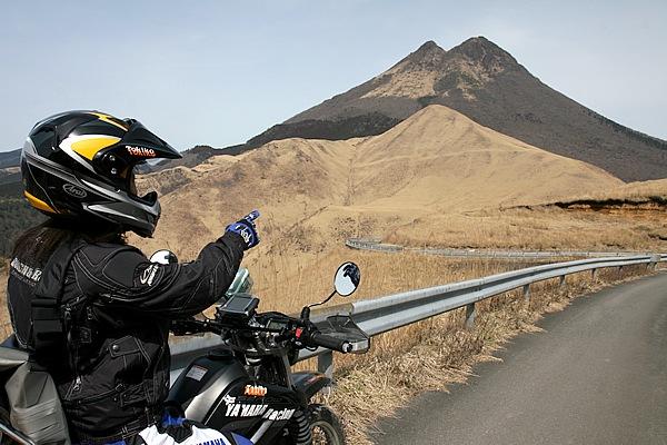 雨乞岳林道から地図中①の分岐に戻る途中。あの2峰をもつ大きな山が由布岳で、豊後富士とも呼ばれる。麓に広がるのが草原です!
