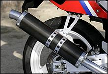 レーシングマシンのイメージを彷彿するカーボン巻きサイレンサーを標準装備。レースシーンでのイメージが市販車に色濃く反映された。